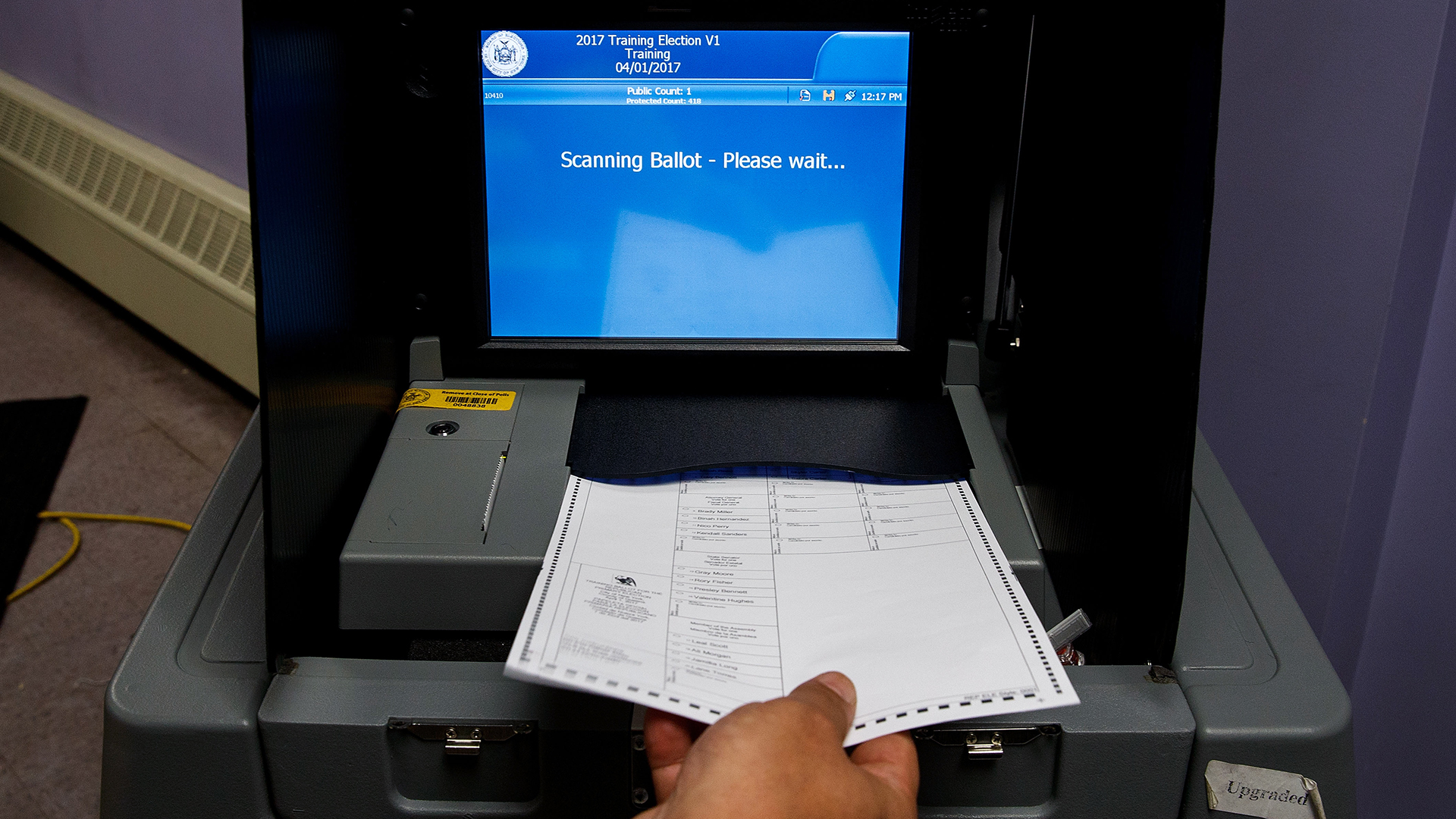 Feeding a ballot into a voting machine-159532.jpg91177702