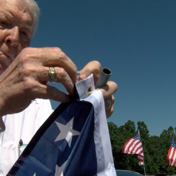 Man repairs and flies American flags on Flag day