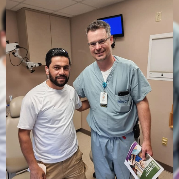 Dlo Yaseen poses with a doctor before ear surgery.